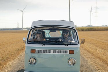 Smiling couple wearing VR glasses driving camper van in rural landscape - GUSF01570