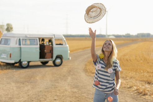 Happy young woman at camper van in rural landscape - GUSF01573
