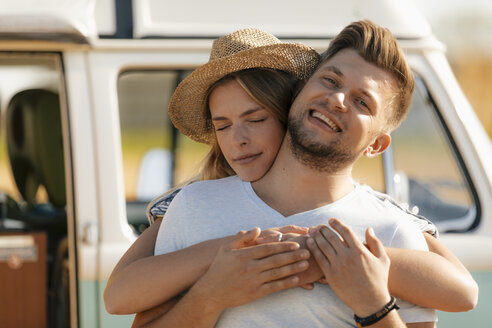 Happy affectionate young couple at camper van - GUSF01576