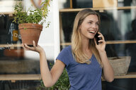 Netherlands, Maastricht, laughing young woman on cell phone in the city holding flowerpot - GUSF01603
