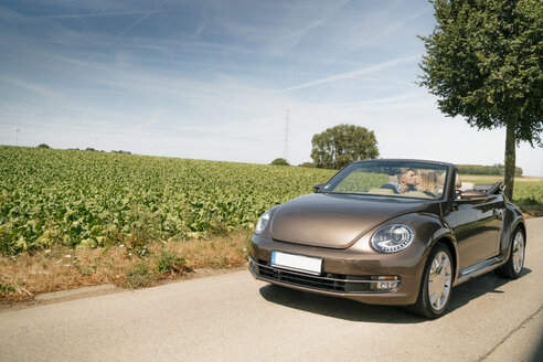 Couple kissing in convertible car on a country road - GUSF01618