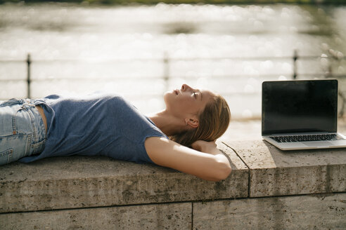 Young woman lying on a wall next to laptop - GUSF01624