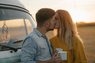Young couple kissing at camper van in rural landscape - GUSF01630