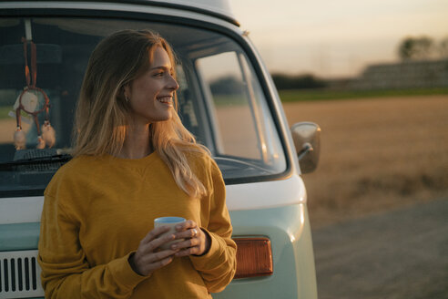Happy young woman holding mug at camper van in rural landscape at sunset - GUSF01633