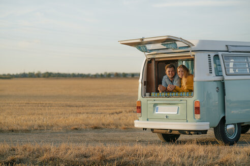 Happy young couple lying in camper van in rural landscape - GUSF01636