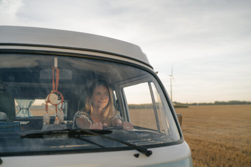 Smiling young woman driving camper van in rural landscape - GUSF01639