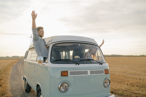 Happy couple leaning out of window of a camper van in rural landscape - GUSF01642