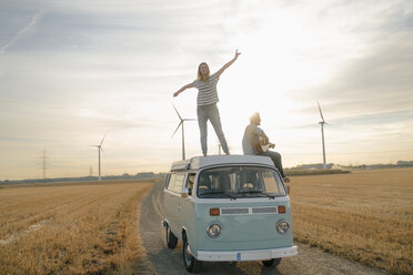 Happy couple with guitar on roof of a camper van in rural landscape - GUSF01645