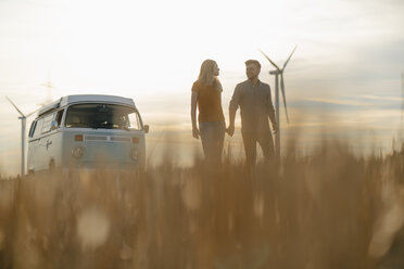 Young couple hand in hand at camper van in rural landscape at sunset - GUSF01648