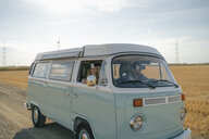 Young couple wearing VR glasses driving camper van in rural landscape - GUSF01651