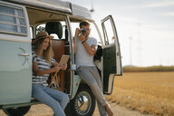 Young couple with tablet and camera at camper van in rural landscape - GUSF01657