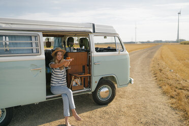 Smiling young woman holding cup of coffee in camper van in rural landscape - GUSF01660