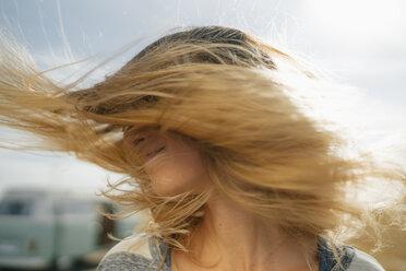 Blong young woman at camper van shaking her hair - GUSF01666