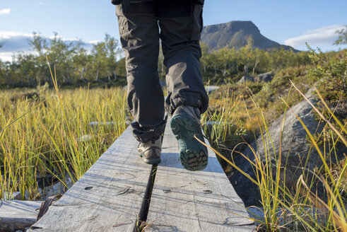 Finland, Lappland, Kilpisjaervi, hiker on boardwalk - PSIF00158
