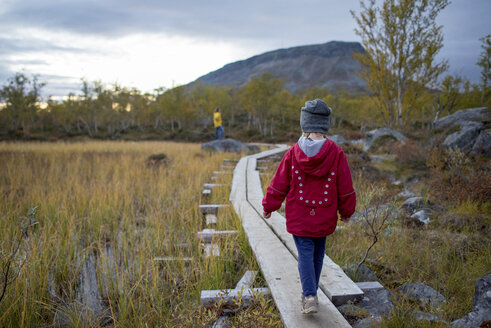 Finland, Lappland, Kilpisjaervi, girl on boardwalk, rear view - PSIF00164