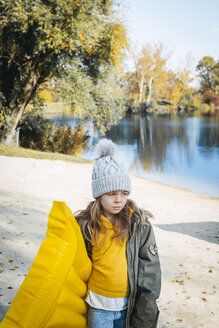 Portrait of girl with yellow airbed on the beach in autumn - HMEF00078