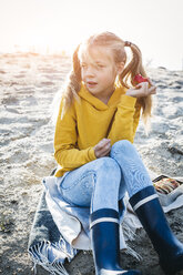 Portrait of girl with plaits sitting on the beach in autumn eating an apple - HMEF00081