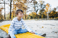 Content little boy sitting on yellow airbed on the beach in autumn - HMEF00084
