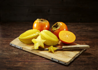 Whole and sliced Kakis and star fruits on wooden board - KSWF01998
