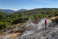 Italy, Tuscany, Colline Metallifere, Val di Cecina, Sasso Pisano, Valle delle Diavolo, hiker looking at geothermal field - LBF02251