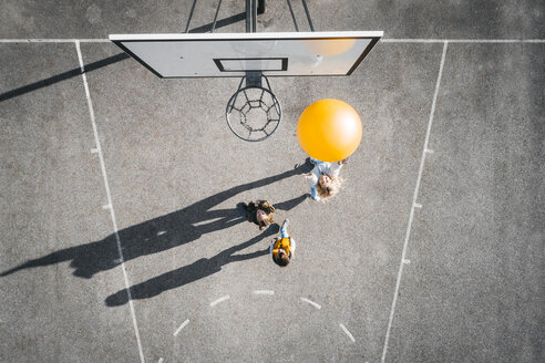 Austria, Aerial view of basketball field, mother and children playing basketball with big ball - HMEF00100
