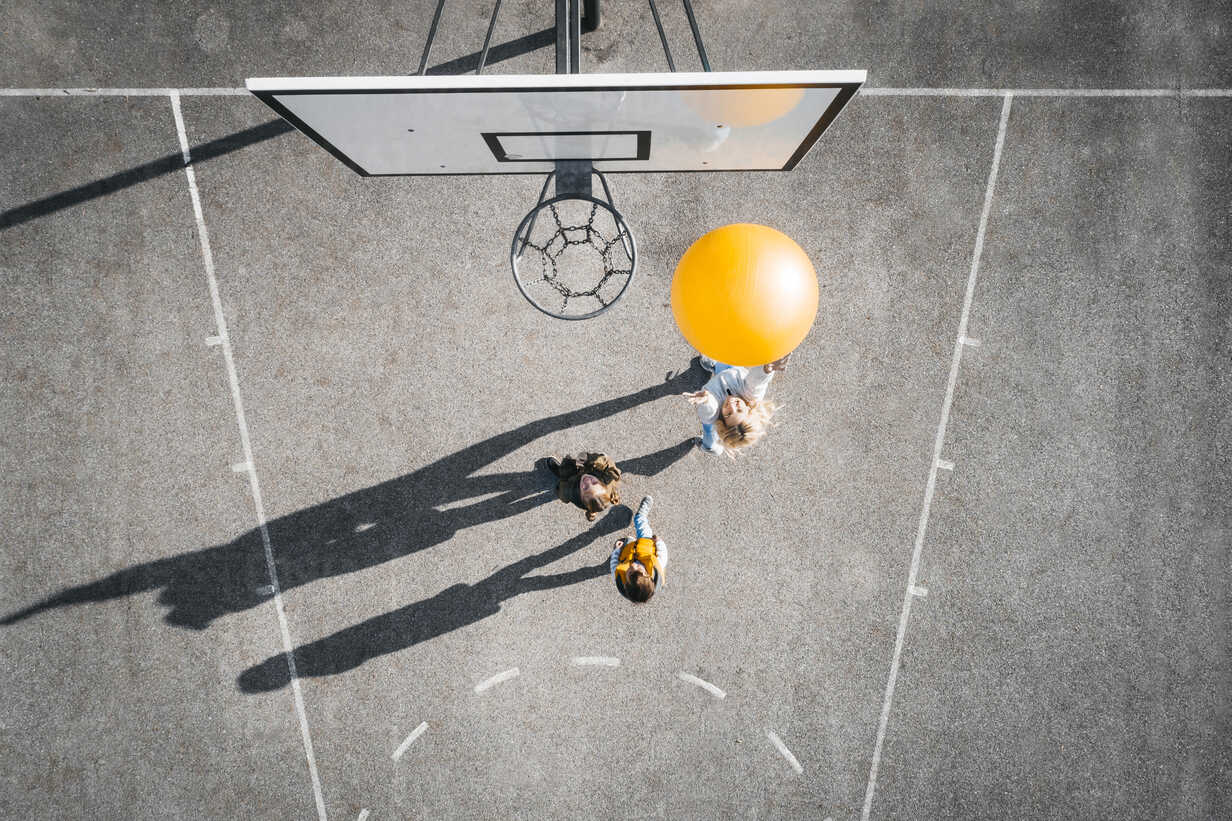 Austria, Aerial view of basketball field, mother and children playing basketball with big ball - HMEF00100 - Epiximages/Westend61