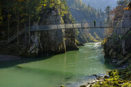Austria, Tyrol, hiker on suspension bridge looking at Tiroler Ache in autumn - LBF02254
