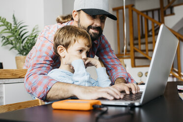 Father and son using laptop together - JRFF01995