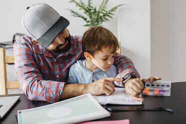 Father texplaining his son the smartwatch, while working at home - JRFF01998