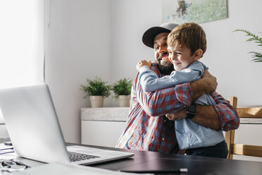 Father sitting at desk, embracing his son - JRFF02001