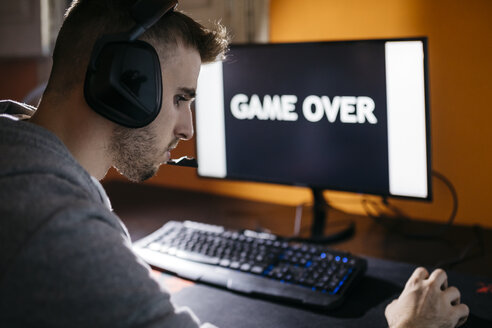 Young man sitting at his PC, looking at screen with game over text - JRFF02022