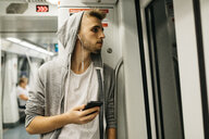 Young man using smartphone in metro - JRFF02028