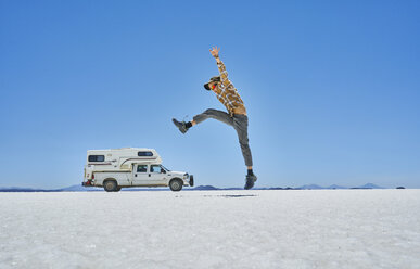 Bolivia, Salar de Uyuni, boy jumping at camper on salt lake - SSCF00018