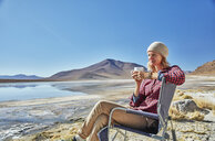 Bolivia, Laguna Colorada, woman sitting on camping chair at lakeshore drinking from cup - SSCF00030