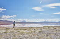 Bolivia, Laguna Colorada, woman standing at lakeshore looking at view - SSCF00036