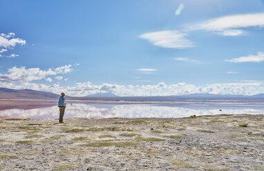 Bolivia, Laguna Colorada, woman standing at lakeshore looking at view - SSCF00036