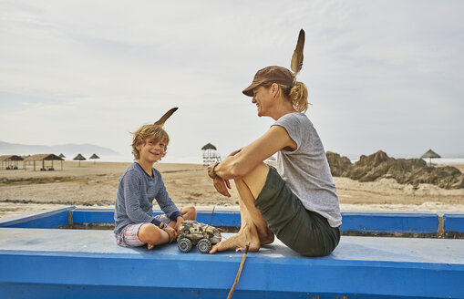 Chile, Arica, happy mother sitting with son on wall on the beach - SSCF00063