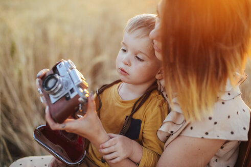 Mother teaching son to photograph with vintage camera on field - CAVF55909