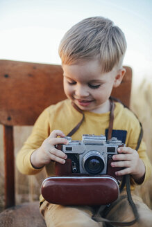 Happy boy with vintage camera sitting on chair amidst field - CAVF55912