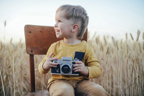 Cheerful boy with camera looking away while sitting on chair amidst wheat field - CAVF55915