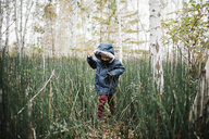 Boy wearing hooded jacket while playing amidst forest - CAVF55969