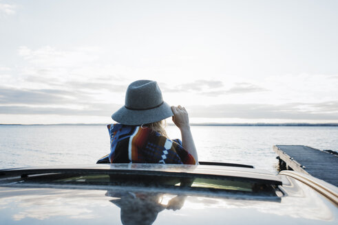 Woman wearing hat looking at view through sun roof against sky - CAVF55975