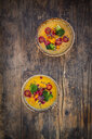 Two bowls of curry dish with Hokkaido pumpkin, broccoli, tomatoes, pomegranate seed and black sesame - LVF07558