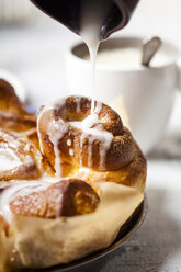 Garnishing home-baked cinnamon buns with icing sugar, close-up - SBDF03849
