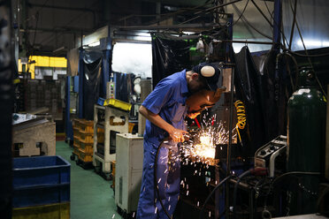 Man wearing blue overall and welding mask standing in factory, welding metal, sparks flying. - MINF09571