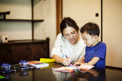 Japanese woman and little boy sitting at a table, drawing with colouring pens. - MINF09583