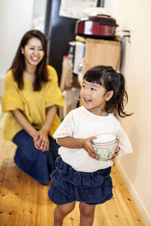 Smiling Japanese woman kneeling in a corridor behind young girl carrying stack of bowls. - MINF09589