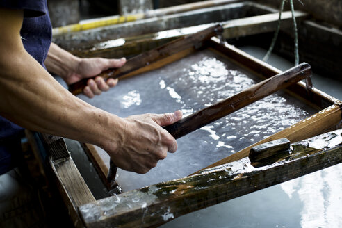 Japanese man in a workshop, holding a wooden frame with pressed pulp, making traditional Washi paper. - MINF09601