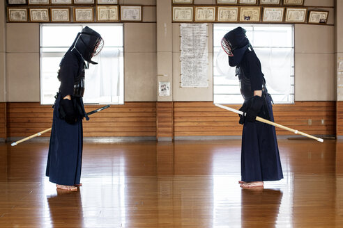 Japanese Kendo fighters standing opposite each other on wooden floor, bowing and greeting. - MINF09616