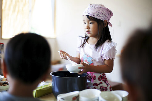 Girl wearing headscarf standing at a table in a Japanese preschool, serving lunch to children. - MINF09625